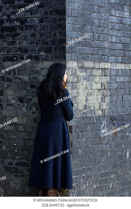 Young woman standing behind a wall outdoors