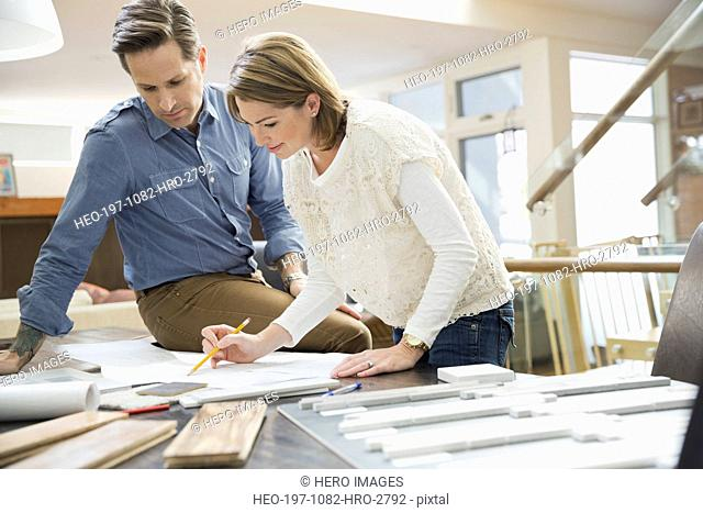 Couple looking at blueprints and wood swatches