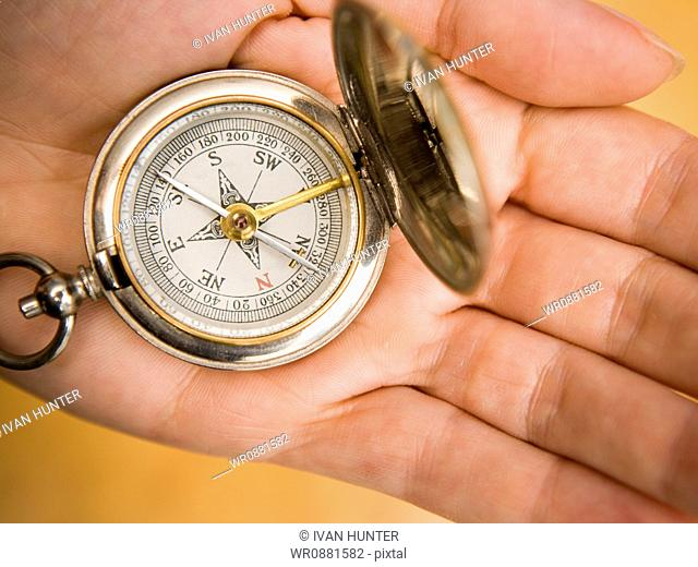 Close-up of a person holding a compass