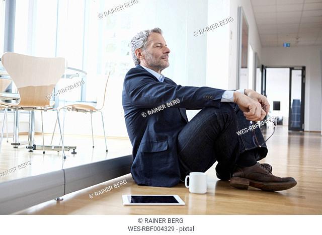 Successful businessman sitting on floor taking a break