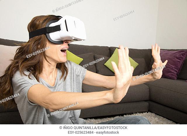 brown hair adult woman with virtual reality headset, or 360 glasses, grey shirt, open mouth scared face expression, indoor home