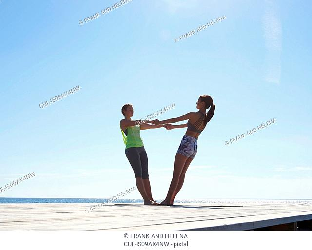 Women on pier face to face holding hands leaning back exercising