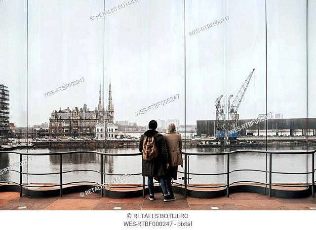 Belgium, Antwerp, back view of couple looking through window to docklands