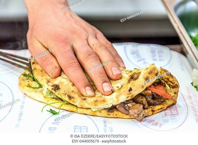 Man hand preparing grilled delicious liver Turkish shish kebab over lavash to serve