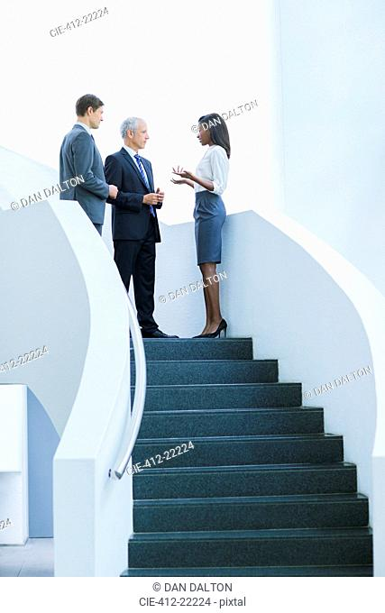 Business people talking on stairs of office building
