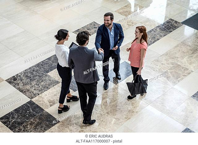Business people greeting each other in hotel lobby