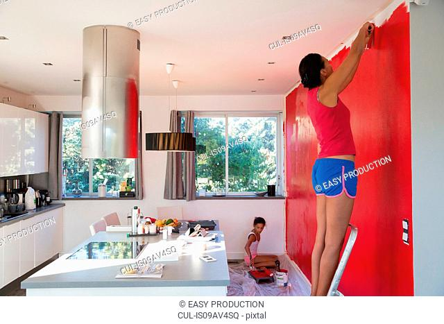 Girl and mother painting kitchen wall red with paint rollers