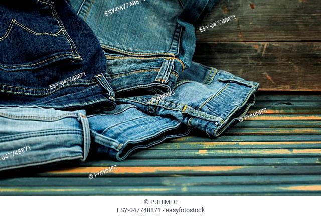 bunch of jeans on a wooden background strewn jeans, close-up, fashionable clothes
