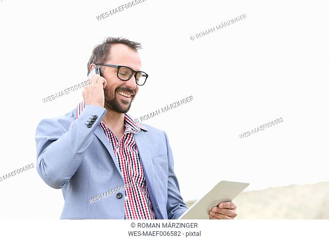 Germany, Bavaria, Businessman talking on mobile phone while using digital tablet, smiling