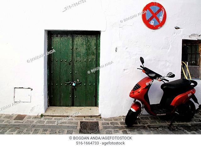 One red motorbikes parked and chained in front of an old white house with a green locked door