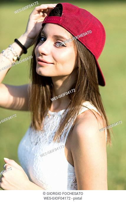 Portrait of smiling young woman wearing baseball cap outdoors