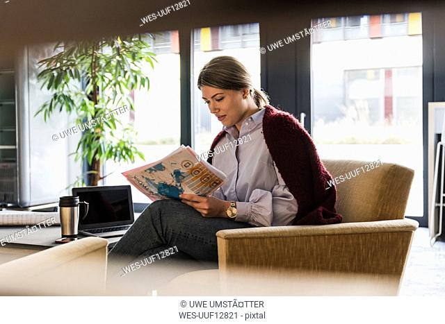 Young woman sitting in armchair reading documents