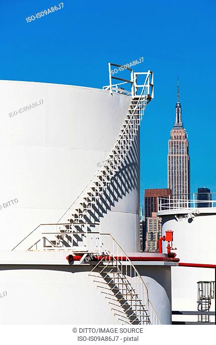 Storage tanks of oil refinery with Empire State building in background, New York, USA
