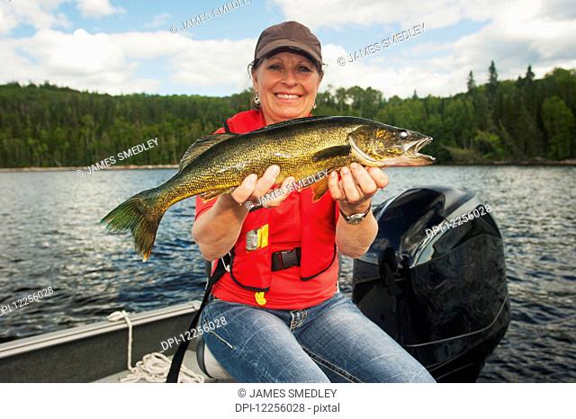 Woman angler holds a summer walleye; Ontario, Canada