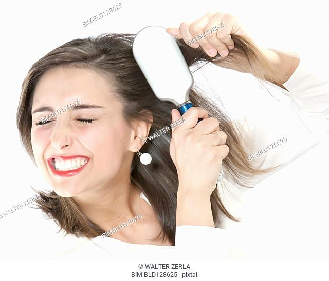 Grimacing woman brushing tangles from hair
