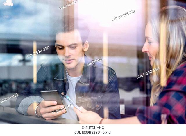 Young students looking at smartphones in cafe window seat, view through window