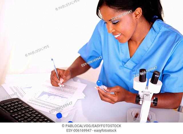 Scientific woman working with test tube and notes at laboratory