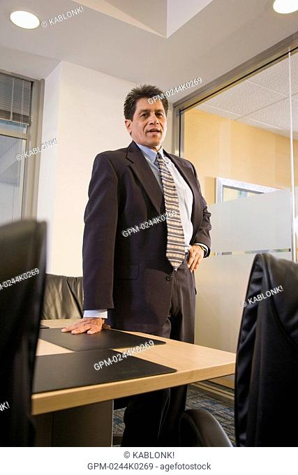 Portrait of Hispanic businessman standing by table in boardroom