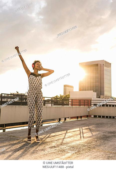Young woman with headphones dancing on rooftop