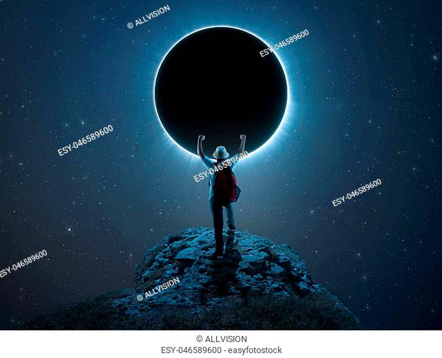 Traveler kid rising his hands on a peak in front of eclipse