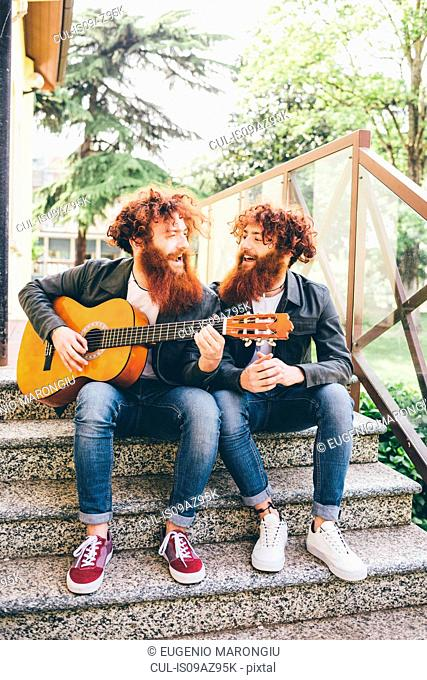 Young male hipster twins with red beards sitting on stairway playing guitar
