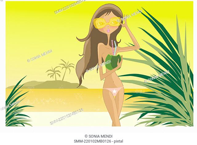 Woman in shades with fruit drink on the beach