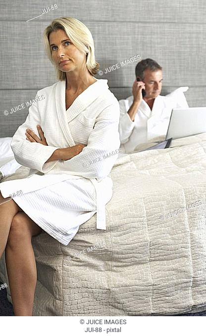 Couple sitting on hotel bed in bathrobes, man using laptop and mobile phone, woman looking bored