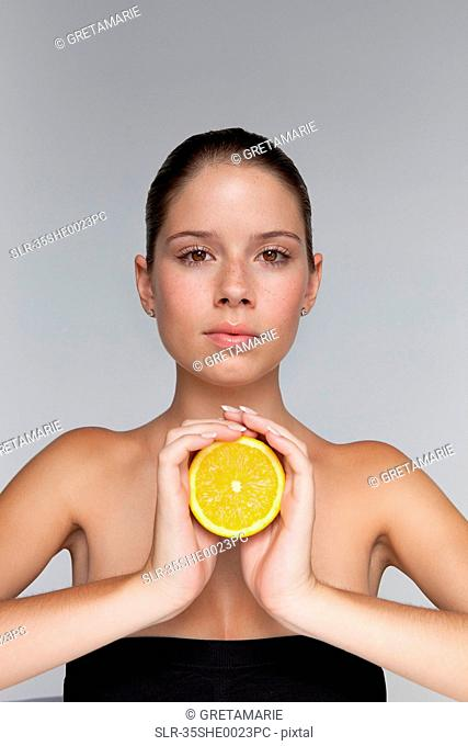Woman holding halved orange