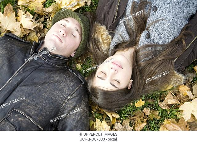 Overhead view of couple lying in autumn leaves