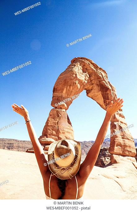 USA, Utah, happy woman looking at Delicate Arch in Arches National Park, back view