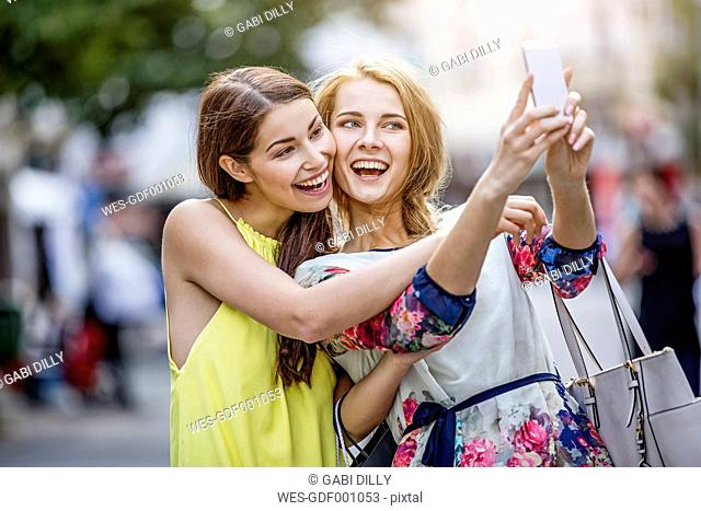 Two happy young women taking a selfie in the city