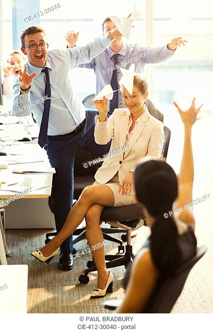 Playful business people throwing paper airplanes at each other in office