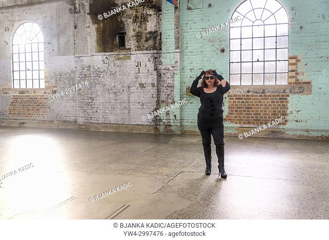 Woman dressed in black with raised arms standing in empty industrial building