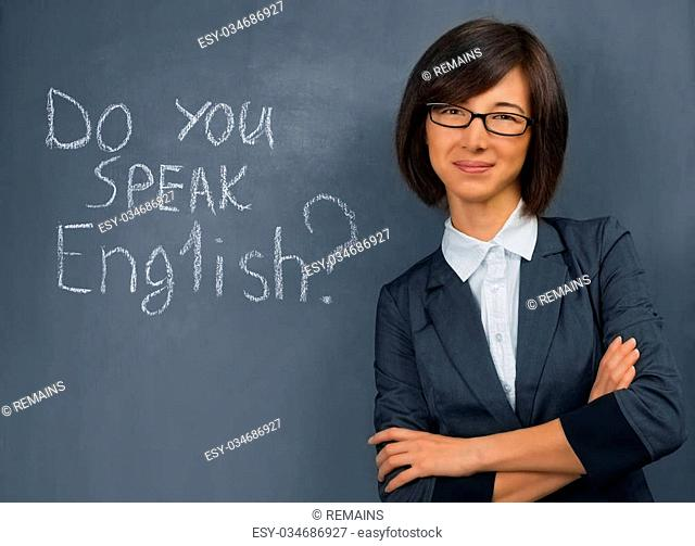 Young woman in a suit standing near the blackboard, English lesson