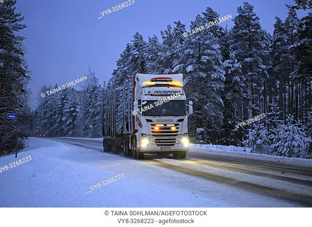 Salo, Finland - January 25, 2019: Scania R520 logging truck of E Nousiainen lights up rural highway in the blue hour of winter dusk