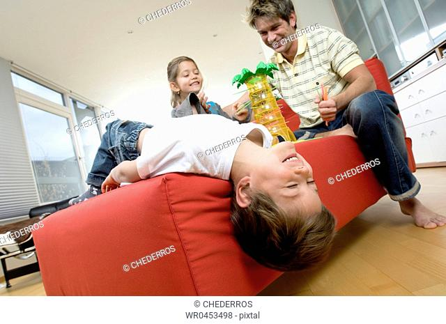 Low angle view of a father with his daughter and son playing on a couch