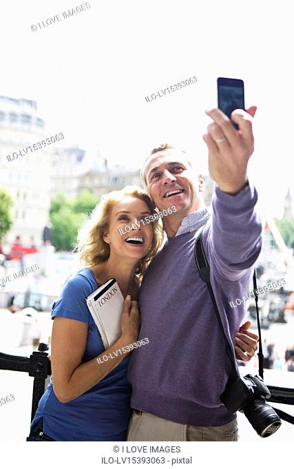 A middle-aged couple standing by Trafalgar Square, taking a photograph of themselves
