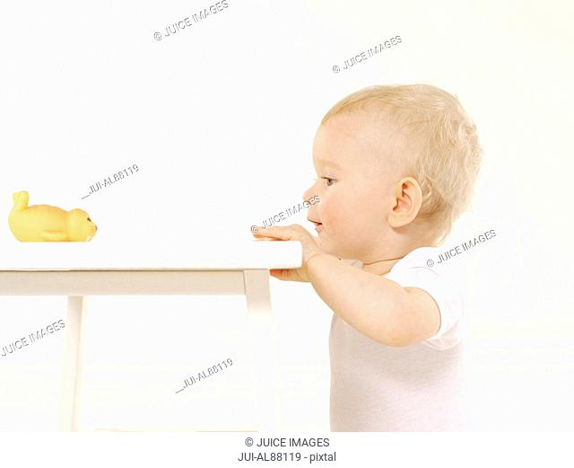 Baby looking at toy on table