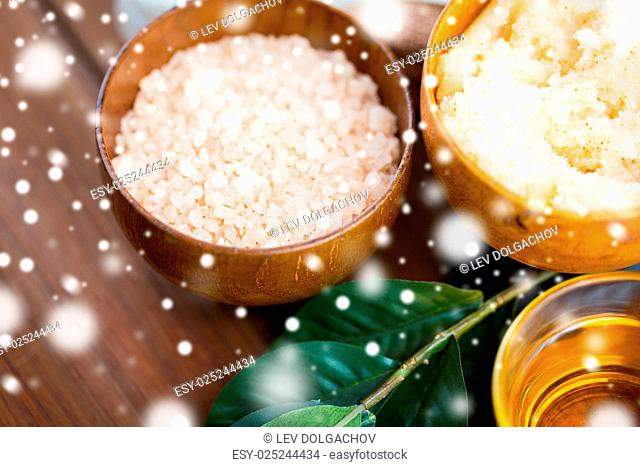 beauty, spa, bodycare, natural cosmetics and and wellness concept - close up of himalayan pink salt and body scrub with leaves on wooden table over snow