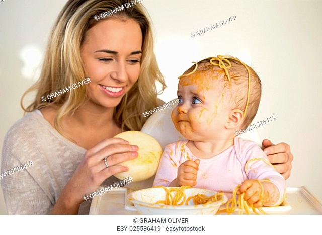 Mother trying to clean her messy baby daughter, who has tipped spaghetti on