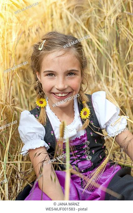 Germany, Saxony, portrait of smiling girl sitting in a field wearing dirndl