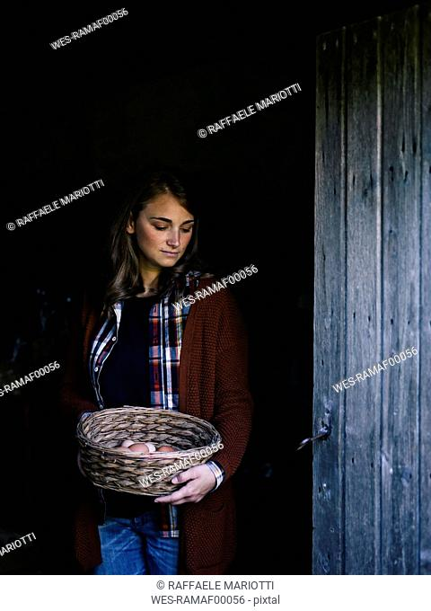 Portrait of woman with basket of fresh eggs