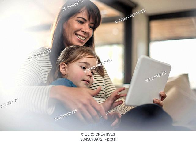 Woman with daughter on sofa looking at digital tablet