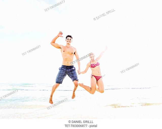 Young couple jumping on beach, holding hands