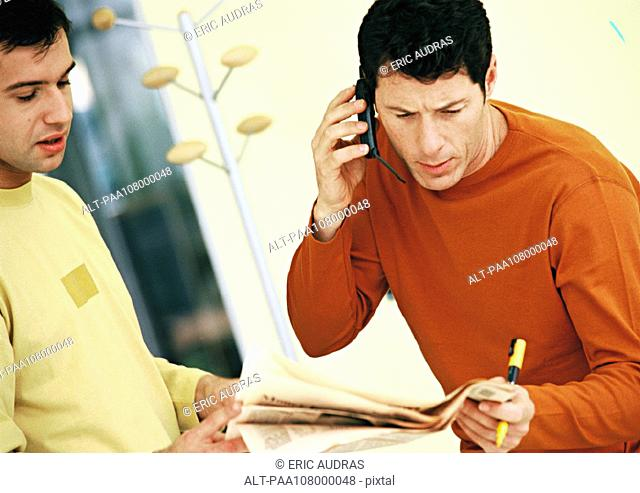 Men looking at newspaper, one using cell phone