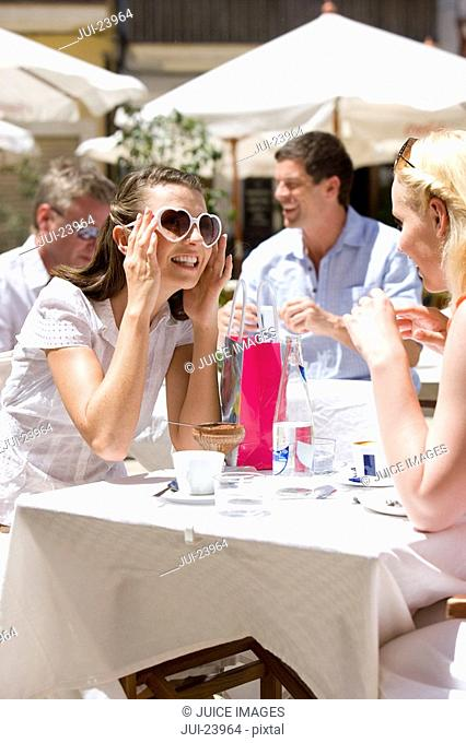 Women wearing heart-shape sunglasses at sunny, outdoor cafŽ
