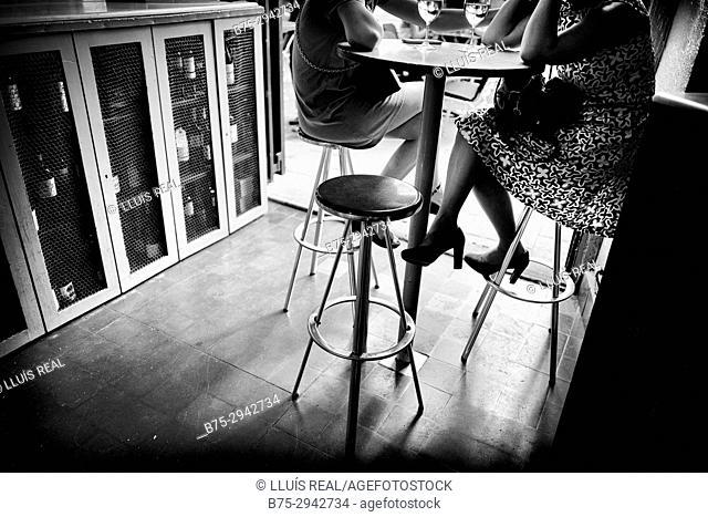 Dos mujeres jovenes irreconocibles tomando una copa de vino en un bar sentadas en un taburete. Barcelona, Catalonia, Spain