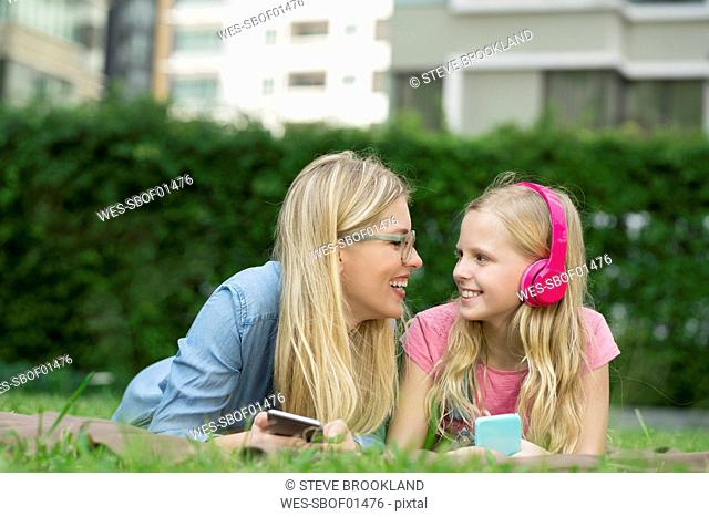 Happy mother and daughter with smartphone and headphones in garden