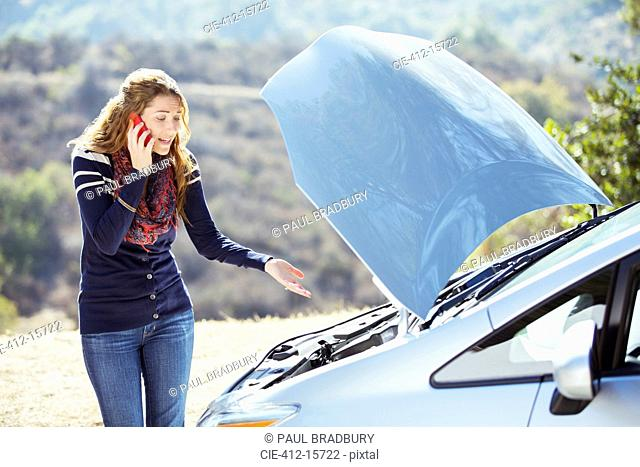 Frustrated woman talking on cell phone with automobile hood raised at roadside
