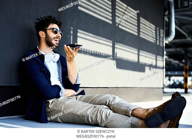 Relaxed young man sitting on ground talking on mobile phone